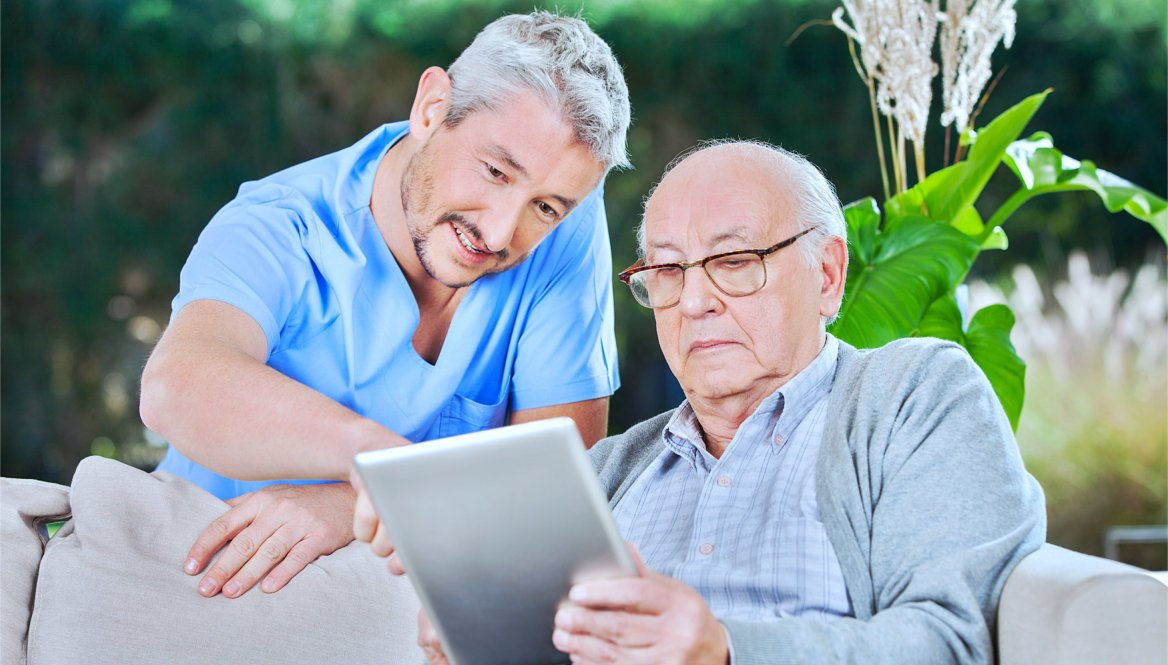 caregiver helping senior in using tablet